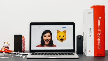 PARIS, FRANKRIJK - SEP 3, 2017: Minimalistische creatieve kamertafel met Safari Browser open op MacPook Pro laptop met Apple Computers website met nieuwste iPhone X 10 met vrouwelijke kat animoji emoji
