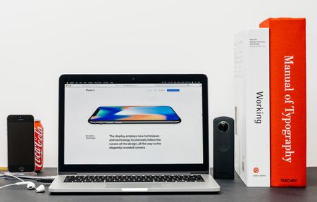 PARIJS, FRANKRIJK - 3 SEP 2017: Minimalistische creatieve kamertafel met Safari Browser open op MacPook Pro-laptop met presentatie van Apple Computers-website met nieuwste iPhone X 10 met afgeronde hoeken dispay