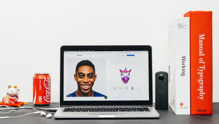 PARIS, FRANCE - SEP 3, 2017: Minimalist creative room table with Safari Browser open on MacPook Pro laptop showcasing Apple Computers website with latest iPhone X 10 with unicorn animoji