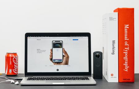 PARIJS, FRANKRIJK - 3 SEP 2017: Minimalistische creatieve kamertafel met Safari Browser open op MacPook Pro-laptop met presentatie van de Apple Computers-website met de nieuwste iPhone X 10 met appel betalen met Face ID