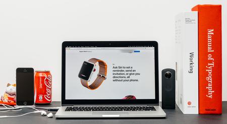 PARIJS, FRANKRIJK - 3 SEP 2017: Minimalistische creatieve kamertafel met Safari Browser op MacPook Pro-laptop op Apple Computers-website met nieuwste Apple Watch-serie 3 met Ask Siri mobiel
