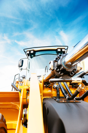 Front view of powerful excavator with beautiful blue sky in the background