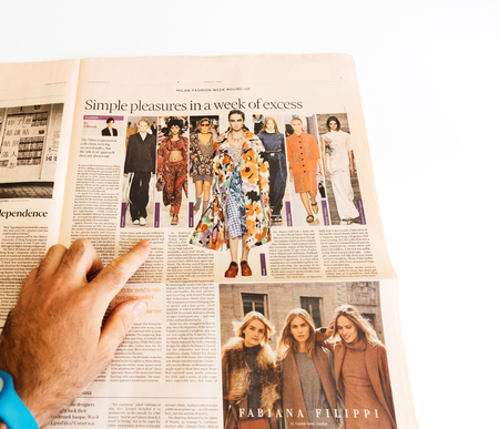 PARIS, FRANCE - SEP 25, 2017: Man reading Financial Times international newspaper about Milan Fashion Week looking at divers styles and looks reading the fashion news
