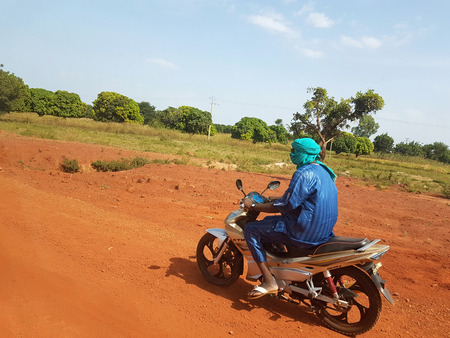 BAMAKO, MALI - DEC 19, 2016: African paysage with Touareg on his KTM bike driving fast ont the red african soil