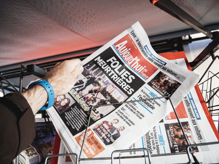 PARIS, FRANCE - OCT 3, 2017: Man buying Aujordhui French newspaper with socking title and photo at press kiosk about the 2017 Las Vegas Strip shooting in United States with about 60 fatalities and 527 injuries
