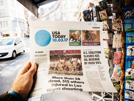 PARIS, FRANCE - OCT 3, 2017: Man buying USA Today newspaper with socking title and photo at press kiosk about the 2017 Las Vegas Strip shooting in United States with about 60 fatalities and 527 injuries Editorial