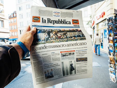PARIS, FRANCE - OCT 3, 2017: Man buying La Republica Italian press newspaper with socking title and photo at press kiosk about the 2017 Las Vegas Strip shooting in United States with about 60 fatalities and 527 injuries Editorial