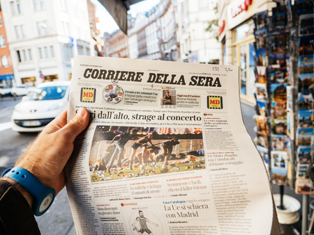 PARIS, FRANCE - OCT 3, 2017: Man buying Corriere della Sera newspaper with socking title and photo at press kiosk about the 2017 Las Vegas Strip shooting in United States with about 60 fatalities and 527 injuries