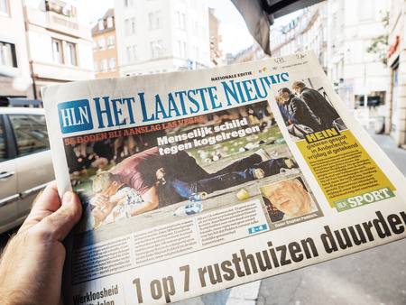 PARIS, FRANCE - OCT 3, 2017: Man buying het laatste nieuws newspaper with socking title and photo at press kiosk about the 2017 Las Vegas Strip shooting in United States with about 60 fatalities and 527 injuries