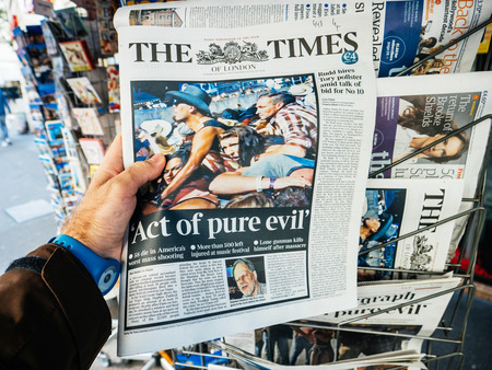 PARIS, FRANCE - OCT 3, 2017: Man buying The Times newspaper with socking title and photo at press kiosk about the 2017 Las Vegas Strip shooting in United States with about 60 fatalities and 527 injuries Editorial