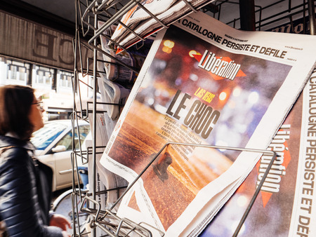 PARIS, FRANCE - OCT 3, 2017: Man buying Liberation French newspaper with socking title and photo at press kiosk about the 2017 Las Vegas Strip shooting in United States with about 60 fatalities and 527 injuries