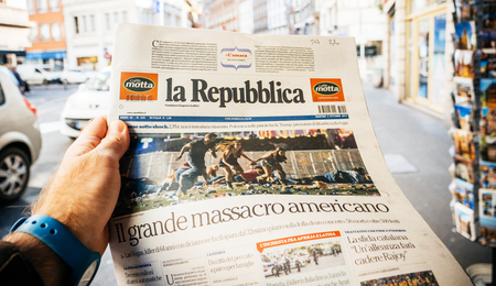 PARIS, FRANCE - OCT 3, 2017: Man buying Italian La Repubblica newspaper with socking title and photo at press kiosk about the 2017 Las Vegas Strip shooting in United States with about 60 fatalities and 527 injuries