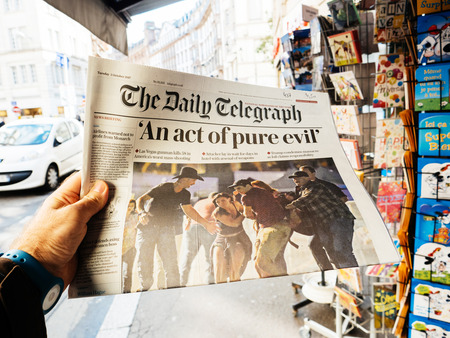 PARIS, FRANCE - OCT 3, 2017: Man buying The Daily Telegraph newspaper with socking title Pure Evil and photo at press kiosk about the 2017 Las Vegas Strip shooting in United States with about 60 fatalities and 527 injuries