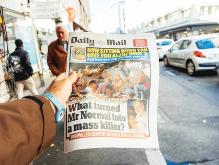 PARIS, FRANCE - OCT 3, 2017: Man buying Daily Dail newspaper with socking title and photo at press kiosk about the 2017 Las Vegas Strip shooting in United States with about 60 fatalities and 527 injuries