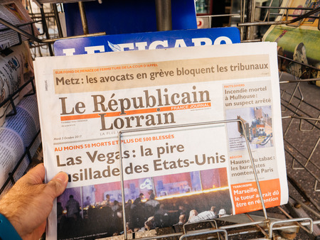 PARIS, FRANCE - OCT 3, 2017: Man buying Le republicai Lorrain newspaper with socking title and photo at press kiosk about the 2017 Las Vegas Strip shooting in United States with about 60 fatalities and 527 injuries