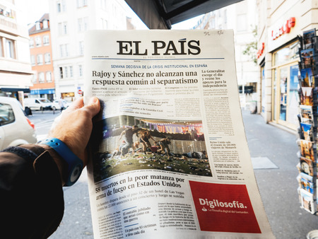 PARIS, FRANCE - OCT 3, 2017: Man buying Spanish El Pais  newspaper with socking title and photo at press kiosk about the 2017 Las Vegas Strip shooting in United States with about 60 fatalities and 527 injuries