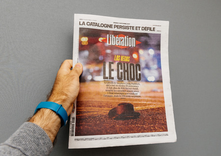 PARIS, FRANCE - OCT 3, 2017: Man holding French Liberation newspaper cover with socking title Pure Evil and photo after Las Vegas Strip shooting in United States