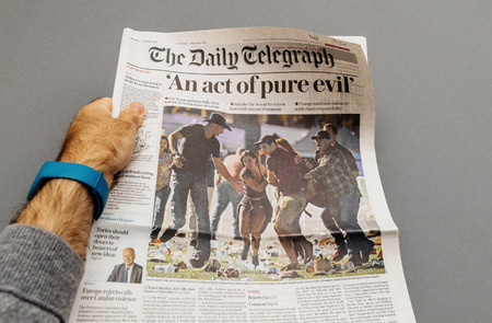 PARIS, FRANCE - OCT 3, 2017: Man holding The Daily Telegraph newspaper cover with socking title Pure Evil and photo after Las Vegas Strip shooting in United States Editorial
