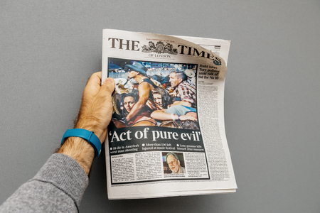 PARIS, FRANCE - OCT 3, 2017: Man holding The Times newspaper cover with socking title Pure Evil and photo after Las Vegas Strip shooting in United States Editorial