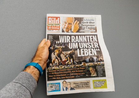 PARIS, FRANCE - OCT 3, 2017: Man holding Die Bild newspaper cover with socking title Pure Evil and photo after Las Vegas Strip shooting in United States