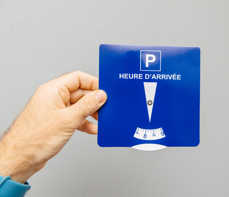 Man holding disk parking with french text Heure darrivee  translated as Arrival time from French language - gray background
