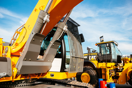 earthmover: PARIS, FRANCE - SEP 5, 2014: Yellow Liebherr excavator and Cat tractor parked on a street near the construction site on a sunny day