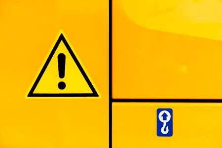 Signe de triangle jaune de l'attention sur le corps du tracteur de construction industrielle jaune