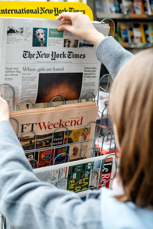 STRASBOURG, FRANCE - OCT 28, 2017: Woman buying The New York Times newspaper business at press kiosk featuring article about Nigerian Girls