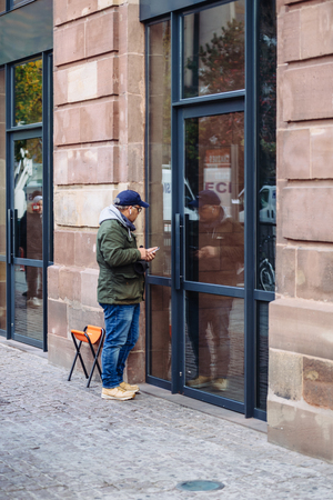 STRASBOURG, FRANCE - NOV 3, 2017: Man with foldable chair at Apple store waiting for the latest Apple iPhone X