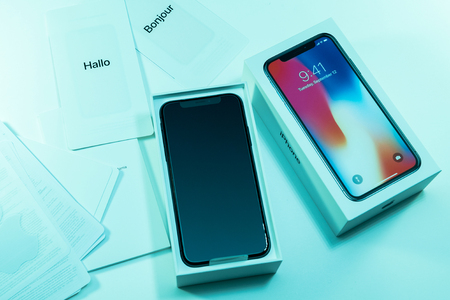 PARIS, FRANCE - NOV 3, 2017: Unboxing unpacking of the latest Apple iPhone X 10 smartphone with accesories on cyan tone table