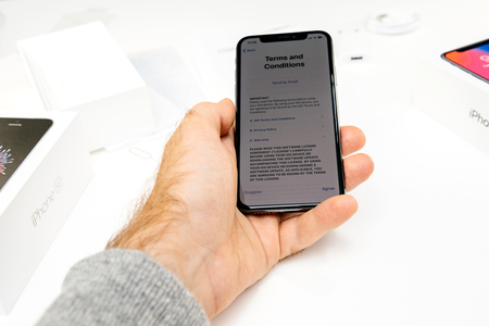 PARIS, FRANCE - NOV 3, 2017: New Apple iPhone X 10 smartphone first run with hand accepting Terms and Conditions of Privacy and warranty