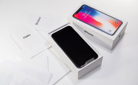 PARIS, FRANCE - NOV 3, 2017: Unboxing unpacking of the latest Apple iPhone X 10 smartphone on white table with accesories instruction manual