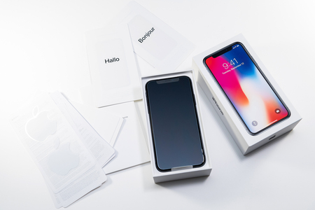 PARIS, FRANCE - NOV 3, 2017: Unboxing unpacking of the latest Apple iPhone X 10 smartphone with accesories on white table Editorial