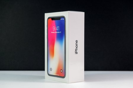 PARIS, FRANCE - NOV 3, 2017: Unboxing unpacking box of the latest Apple iPhone X 10 smartphone against black background