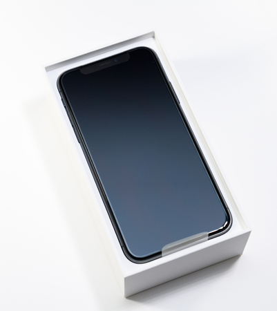 PARIS, FRANCE - NOV 3, 2017: Unboxing unpacking of the latest Apple iPhone X 10 smartphone on white table Editorial