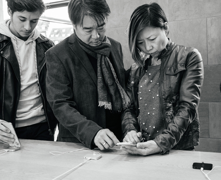 STRASBOURG, FRANCE - NOV 3, 2017: Asian ethnicity couple customers at Apple Store Computers admiring deciding to buy the latest iPhone X 10 smartphone telephone