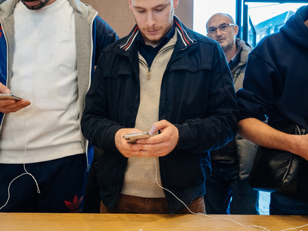 STRASBOURG, FRANCE - NOV 3, 2017: Male customer friends comparing the new iPhone X with other smartphones during the launch day of the latest iPhone