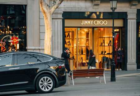 BARCELONA, SPAIN - NOV 13, 2017: Luxury electric Tesla Model X SUV parked in front of the Jimmy Choo fashion boutique clothes store on Avenue Diagonal Editorial