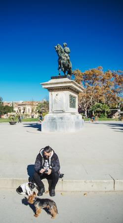 BARCELONA, SPAIN - NOV 12, 2017: Spanish man with two small dogs using smartphone near Estatua equestre del general Prim statue monument in Parc de la Ciutadella on a warm summer sunny day Editorial