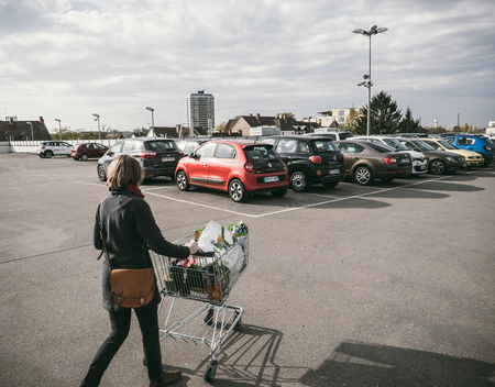 FRANKFURT, GERMANY - NOV 4, 2017: Woman pushing supermarket cart full with food and household products tot he car parked on the roof parking