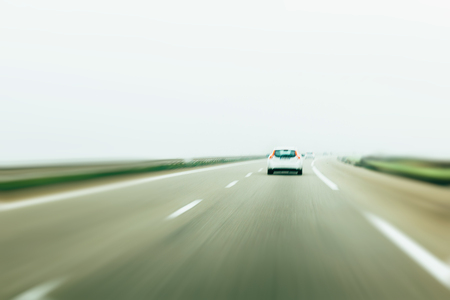 Rear view of white white car driving on German autobahn - fast motion in safety condition during heavy mist 版權商用圖片