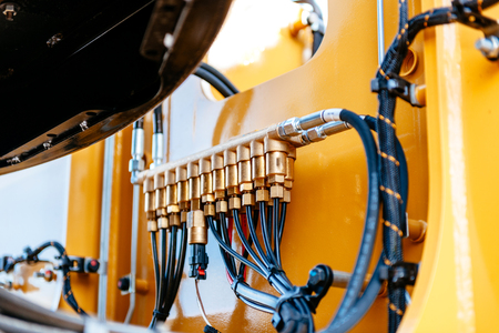 Pipes and tubes of the hydraulic system of a modern excavator tractor - engineering of powerful details of the work machine  Archivio Fotografico