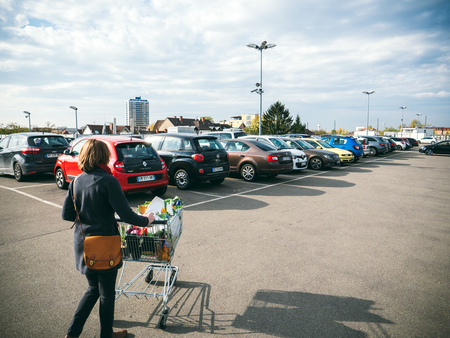 FRANKFURT, GERMANY - NOV 4, 2017: Elevated view of woman pushing supermarket cart full with food and household products tot he car parked on the roof parking