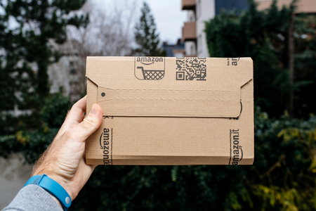 PARIS, FRANCE - NOV 28, 2017: Male hand holding the Amazon cardboard box as he picked it from the front door with trees and houses in the background