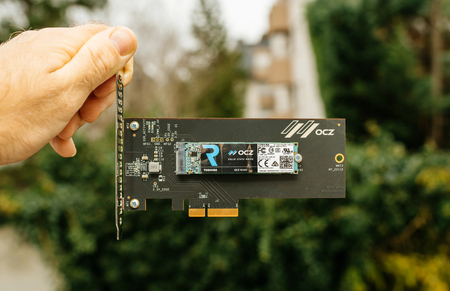 PARIS, FRANCE - NOV 28, 2017: Man hand holding NVME PCIE SSD hard drive disk with itsh adapter to the PCIE slot made by Toshiba OCZ RD400 with high read and write speed