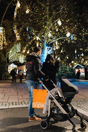 STRASBOURG, FRANCE - NOV 29, 2017: Young couple with pram stroller admiring the Christmas illumination and decorations of the magic Christmas Market in Strasbourg, Alsace at night