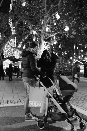 STRASBOURG, FRANCE - NOV 29, 2017: Black and white image of young couple with pram stroller admiring the Christmas illumination and decorations of the magic Christmas Market in Strasbourg, Alsace at night Sajtókép