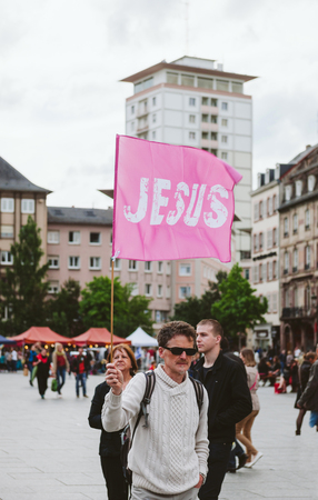 STRASBOURG, FRANCE - MAY 30, 2015: Man with pink Jesus flag at March for Jesus the annual interdenominational event by Christians worldwide