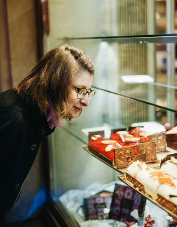 Woman buying sweets a the patisserie bakery store window in French city during Christmas winter holidays