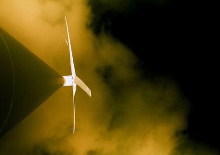 Night view from below of large electric environmentally friendly wind turbine with temepst blue sky and aeroplane near the blade - unusual angle